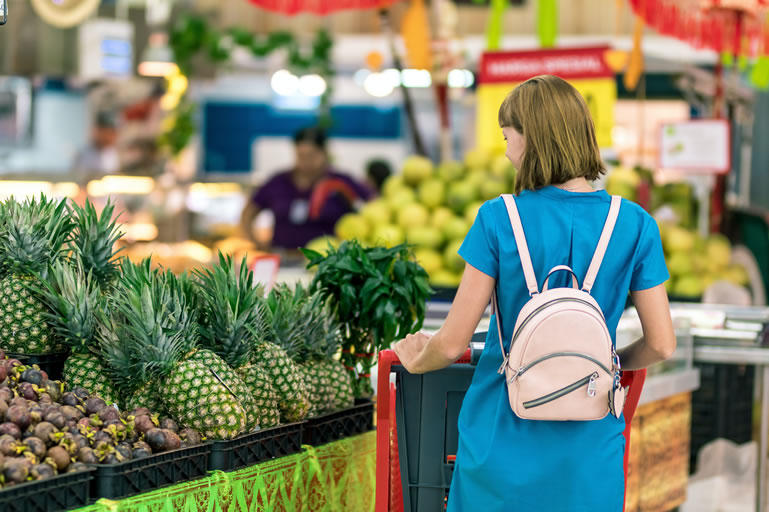 Women in supermarket aisle social distance
